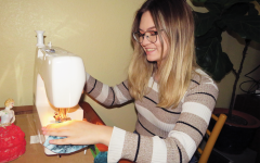 Sydney Driskell sits at her table and uses different colorful fabrics to make masks.